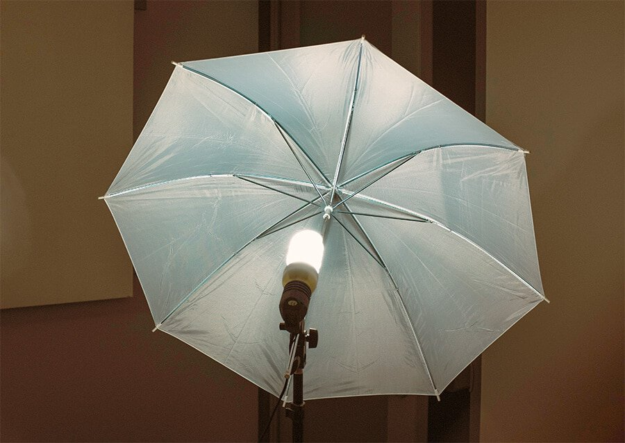 Umbrella light with spiral fluorescent light bulb mounted on a light stand. One of the four different types of photography umbrellas.