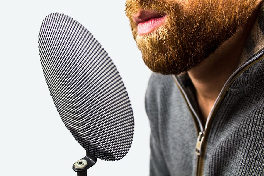 A metal mesh pop filter being used by a voiceover artist