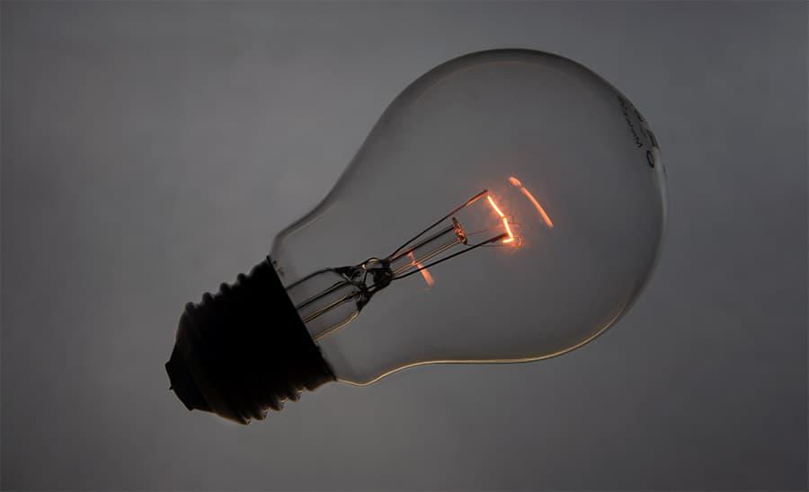 Incandescent tungsten light bulb glows orange