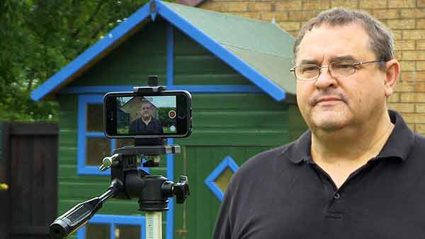 An image of me filming myself using the Filmic Pro video app on an iPhone SE. Clearly, I cannot see the phone's display since I'm using the higher quality rear facing camera. This makes framing myself a problem. Filmic Remote offers a solution, since it can mirror the display of my iPhone and allow remote control of Filmic Pro.